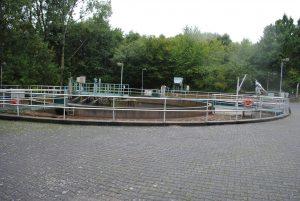 Die Abwasserreinigungsanlage (ARA) Ruppertshain gehört zu den 6 kleineren Anlagen des Abwasserverbandes Main-Taunus mit jeweils weniger als 10.000 EW. Die erste Anlage wurde 1957 für 1.500 EW gebaut und 1980/1982 auf 4.950 EW erweitert. Diese Zahlen verstehen zunächst nur Fachleute. Aber auch ihr werdet gleich wissen, was das bedeutet. Die Größe einer Anlage wird von den Fachleuten der Wasserwirtschaft nach dem Einwohnerwert (EW) gemessen. Falls nur Haushalte an das Kanalnetz angeschlossen wären, würde der Einwohnerwert der Einwohnerzahl (E) entsprechen. Es muss aber auch noch Abwasser aus Betrieben berücksichtigt werden. Dafür gibt es den Einwohnergleichwert (EGW). Wenn zum Beispiel ein Betrieb soviel Schmutzwasser einleitet wie 100 Einwohner, ist der EGW gleich 100. Die Einwohnerzahl und der Einwohnergleichwert ergeben den Einwohnerwert (EW = E + EGW). Ruppertshain hat ungefähr 2.100 Einwohner. Damit verbleibt rechnerisch noch eine Kapazität von 2.850 EW für gewerbliche Abwässer. Bei der Planung der Größe von solchen Anlagen wird jedoch immer auch noch ein erwartetes Einwohnerwachstum und die Ansiedlung neuer Betriebe mit berücksichtigt.